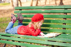 Little girl reading a book  in the park. Stock Photo