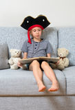 Little girl reading book. Little girl in pirate costume reading book with her plush friends Stock Photo