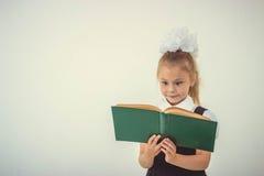 Little girl reading book, preparing for school Stock Images