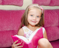 Little girl reading a book and siting on the sofa Stock Photos