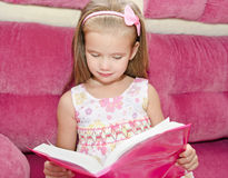 Little girl reading a book and siting on the sofa Royalty Free Stock Images