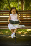 Little girl reading a book sitting on a bench in the park. Outdoor portrait of an adorable young little girl reading a book sitting on a bench in the park Royalty Free Stock Images