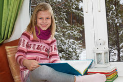 Little girl reading a book sitting on the window on Christm Royalty Free Stock Image
