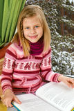 Little girl reading a book sitting on the window on Christm Royalty Free Stock Photo
