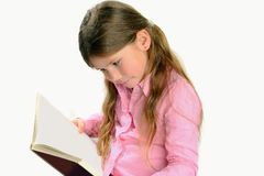 Little  girl reading a book and smiling Royalty Free Stock Photo