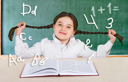 Little girl reading a book smiling teenager near a school board. At a desk in the classroom Stock Photography