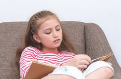 Little girl reading book on sofa. Little girl is reading book on sofa Stock Photos