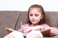 Little girl reading book on sofa. Little girl is reading book on sofa Stock Images