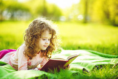 Little girl reading a book in the spring park. Toning photo royalty free stock photos