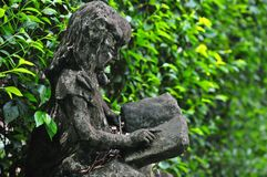 Little girl reading book statue in front of green tree wall in the garden royalty free stock photos