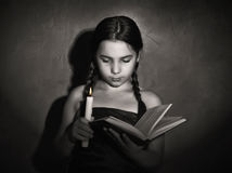 Little girl reading book and studying in candle light in dark room Stock Image