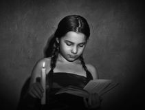 Little girl reading book and studying in candle light in dark room Royalty Free Stock Image