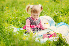 Little girl reading a book in the summer park Stock Photo
