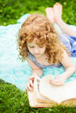 Little girl reading a book in the summer park Royalty Free Stock Image
