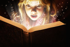Little girl reading. A little girl reading a book with a surprised expression stock images
