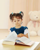 Little girl reading a book at the table. Royalty Free Stock Photography