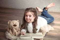 Little girl reading a book with a Teddy bear on the floor, concept of relaxation and friendship stock images