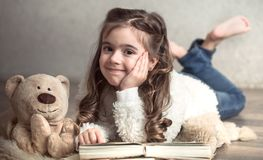 Little girl reading a book with a Teddy bear on the floor, concept of relaxation and friendship. Little girl reading a book with a Teddy bear on the floor in a royalty free stock photos