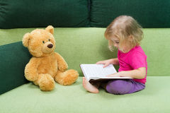 Little girl reading a book Teddy bear. Stock Photos