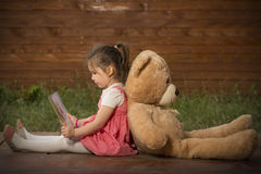 Little girl reading a book to her teddy bear. Beautiful little girl sitting back with toy bear outside in backyard playground, reading to her little plush friend Royalty Free Stock Photo