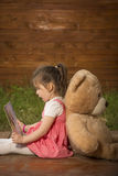 Little girl reading a book to her teddy bear Stock Photography