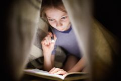 Little girl is reading a book under a blanket with a flashlight in a dark room at night Stock Photos