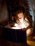 Little girl reading book under blanket at night Stock Images