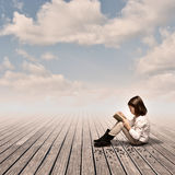 Little girl reading a book. On a wharf Royalty Free Stock Image