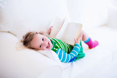 Little girl reading a book on a white couch Royalty Free Stock Photos