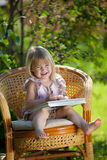 Little girl reading book in wicker chair outdoor Royalty Free Stock Image