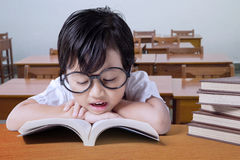 Little girl reading books on desk in class Royalty Free Stock Image