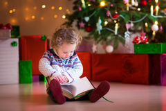 Little girl reading at Christmas tree Stock Photo