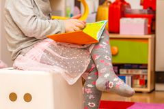 Little girl reading colourful book. With pictures and text Stock Images