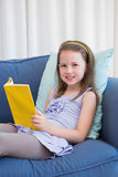 Little girl reading on couch Royalty Free Stock Photos