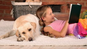 Little girl reading on the floor lyingn on her doggy pillow stock footage