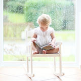 Little girl reading in front of big window Royalty Free Stock Images