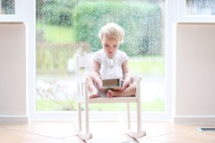 Little girl reading in front of big window Royalty Free Stock Photos
