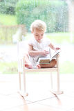 Little girl reading in front of big window Royalty Free Stock Photography
