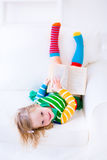 Little girl reading. Happy laughing little girl reading a book relaxing on a white couch at home stock photos