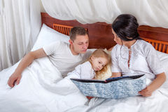 Little girl reading with her parents in bed Stock Photography