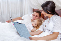 Little girl reading with her parents in bed Stock Photos