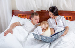 Little girl reading with her parents in bed Stock Photo