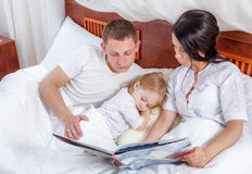 Little girl reading with her parents in bed Stock Image