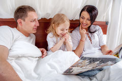 Little girl reading with her parents in bed Stock Images