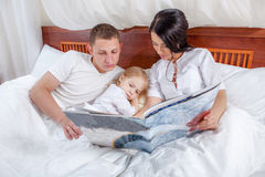 Little girl reading with her parents in bed Royalty Free Stock Photos