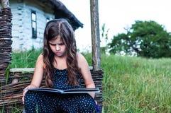 Little girl reading an interesting book Stock Photos