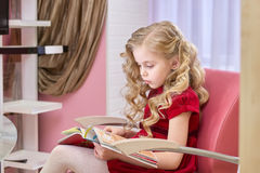 Little girl reading magazine. Child in a hairdressing salon. Reasons why children should read Stock Photography
