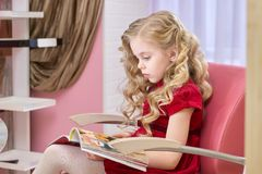 Little girl reading a magazine. Kid in a hairdressing salon Royalty Free Stock Image