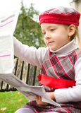 Little girl is reading a newspaper Stock Photos