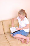 Little girl reading a note Stock Images